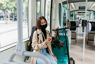 Mid adult woman wearing face mask using mobile phone while sitting with electric push scooter in tram - p300m2226806 by Valentina Barreto