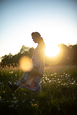 Woman stepping through a meadow - p310m2288440 by Astrid Doerenbruch