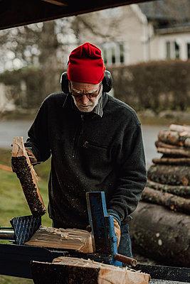 Senior man sawing wood - p312m2191263 by Jennifer Nilsson
