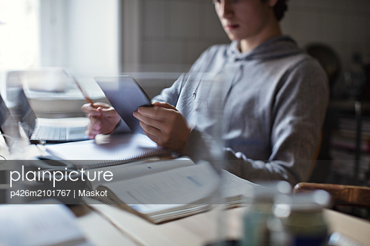Teenage boy using digital tablet while studying at home - p426m2101767 by Maskot