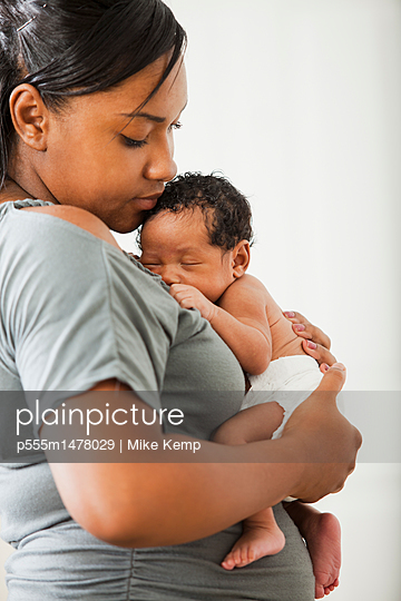 Mixed race mother holding newborn baby - p555m1478029 by Mike Kemp