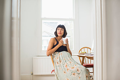 Thoughtful pregnant woman drinking tea in apartment - p1023m2187347 by Sam Edwards