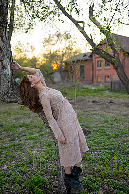 Young woman leaning against a tree, portrait - p1646m2277861 by Slava Chistyakov