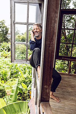 Laughing man on cell phone sitting in the window in tropical surrounding - p300m2103579 by Maya Claussen