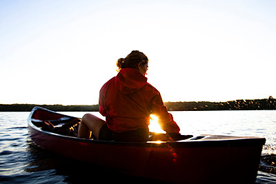 A woman canoes on Cobbosseecontee Lake, in southern Maine - p3436899f by Kyle Sparks