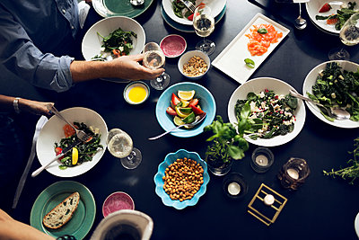 Cropped image of friends eating food at table - p426m1147993 by Maskot