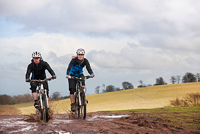 Couple riding bike through muddy puddles - p42911561f by Colin Hawkins