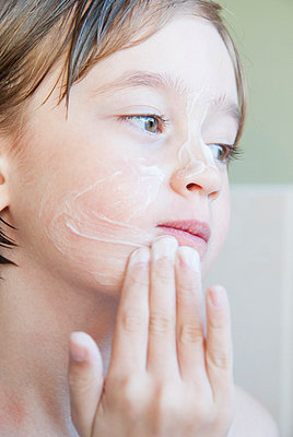 Girl rubbing moisturizer on her face - p429m757568f by Luka photography