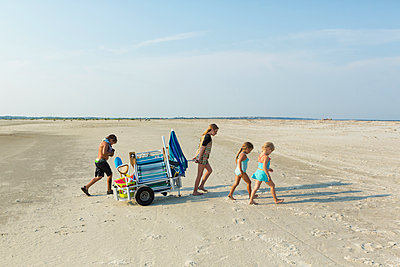 Caucasian boy and girls pulling cart on beach - p555m1522783 by Marc Romanelli