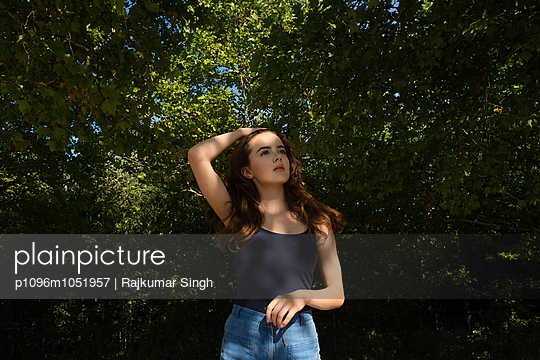 Girl in tank top and shorts in the woods - p1096m1051957 by Rajkumar Singh