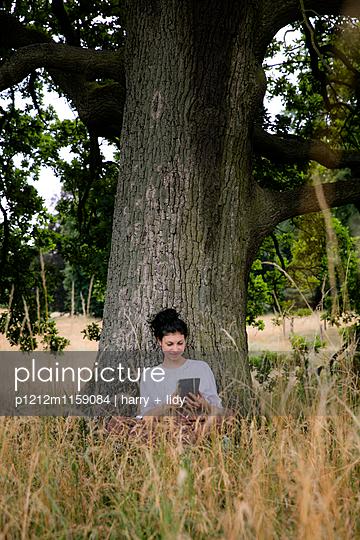 Junge Frau sitzt unter einem Baum - Tablet - p1212m1159084 von harry + lidy