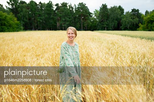 Smiling woman in cornfield, portrait - p1646m2258908 by Slava Chistyakov