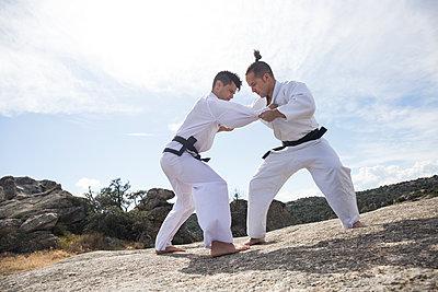 Men doing combat exercises during a martial arts training - p300m1470152 by Andrés Benitez