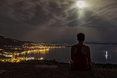 Greece, Pagasetic Gulf, Woman enjoying view to Volos at night, full moon - p300m1581632 von Maria Maar