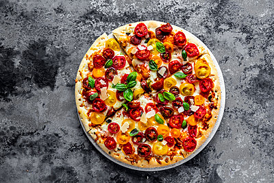 Sliced pizza with tomatoes and basil leaves - p300m2023496 von Sandra Roesch