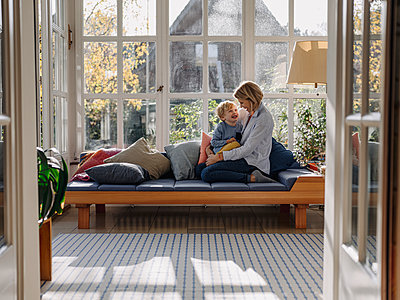 Happy mother and son in sunroom at home - p300m2205492 by Kniel Synnatzschke