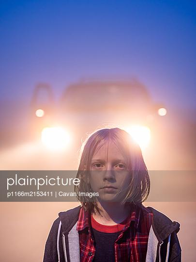 Portrait of tween with shoulder length hair backlit by headlights - p1166m2153411 by Cavan Images