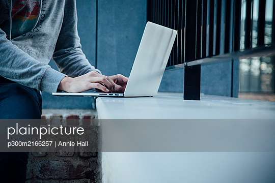 Teenager using laptop in the city - p300m2166257 by Annie Hall
