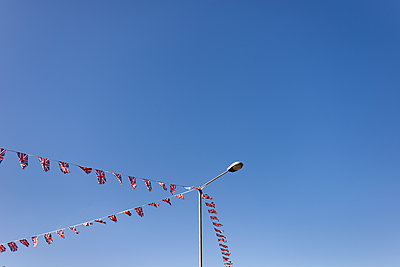 Union Jack buntings against blue sky - p1335m1586382 by Daniel Cullen