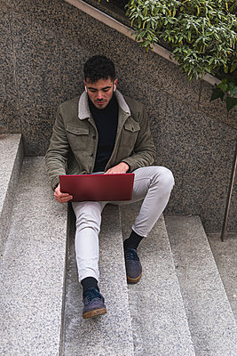 Businessman working on laptop while sitting on steps - p300m2277187 by Josu Acosta