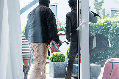 Two burglars leaving an one-family house with their loot at daytime - p300m965554f by noonland