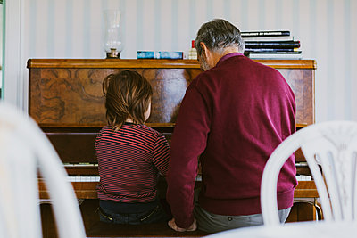 Rear view of boy playing piano with great grandfather at home - p426m1468225 by Maskot