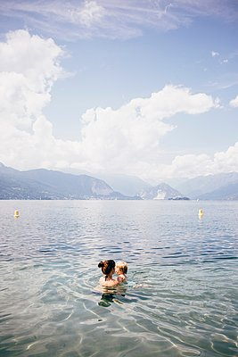 Head and shoulders of mother holding son in lake, Luino, Lombardy, Italy - p429m1105634 by JFCreatives