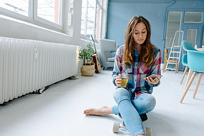 Young woman reading SMS on smartphone  - p586m1510357 by Kniel Synnatzschke