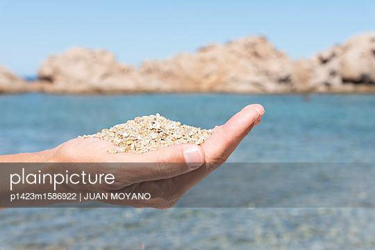 Person hält Sand in der Hand - p1423m1586922 von JUAN MOYANO