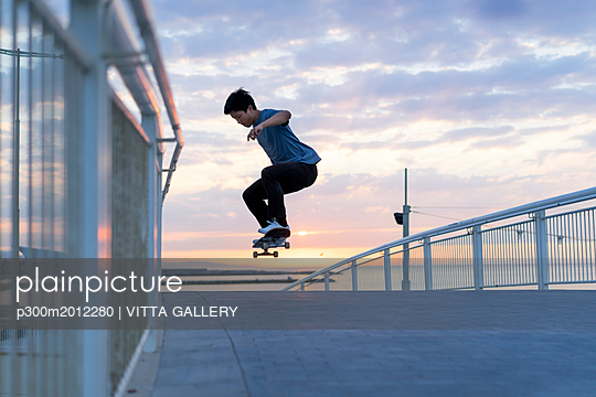 Young Chinese man skateboarding at sunsrise near the beach - p300m2012280 von VITTA GALLERY