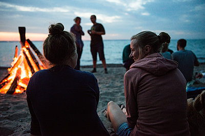 Friends sitting by campfire on beach - p1142m1362246 by Runar Lind