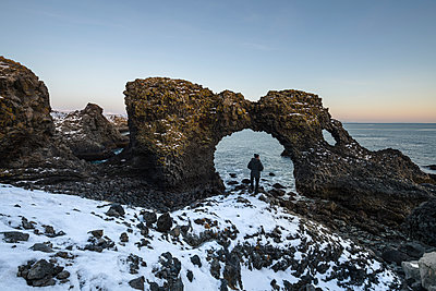 Rear view of hiker standing by natural arch at beach during winter - p1166m1542563 by Cavan Social