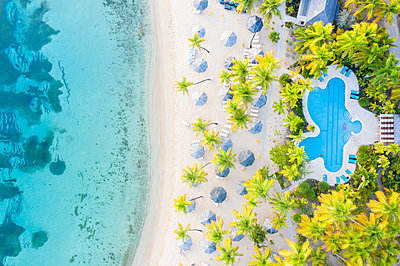 Swimming pool and beach umbrellas on white sand beach from above by drone, Morris Bay, Old Road, Antigua, Leeward Islands, West Indies, Caribbean - p871m2143269 by Roberto Moiola