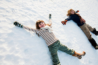 Children making snow angels - p9243107f by Image Source