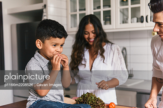 Young boy smiling whiling eating lunch in kitchen with mom and dad - p1166m2208526 by Cavan Images