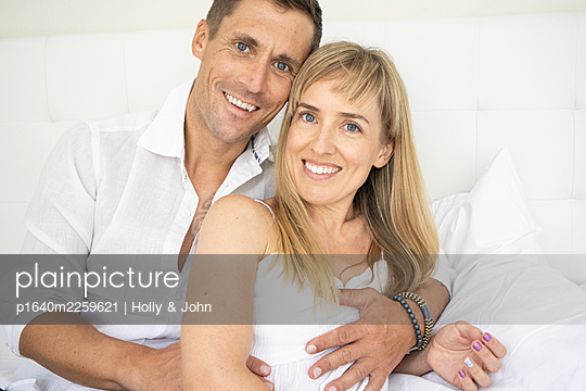 Happy couple sitting on bed, portrait - p1640m2259621 by Holly & John
