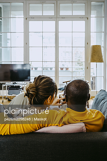 Rear view of girlfriend and boyfriend sitting together on sofa in living room at home - p426m2298248 by Maskot