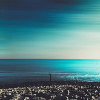 Germany, Lower Saxony, Neuharlingersiel, Silhouette of man standing alone on rocky coastal beach - p300m2198047 by Dirk Wüstenhagen