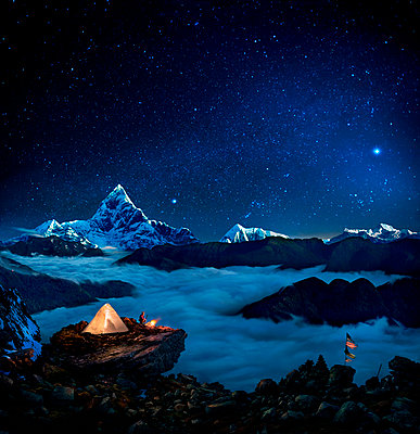 Starry sky over camper at bonfire overlooking sea of clouds and mountains, Pokhara, Kaski, Nepal - p343m2028883 by Per-Andre Hoffmann
