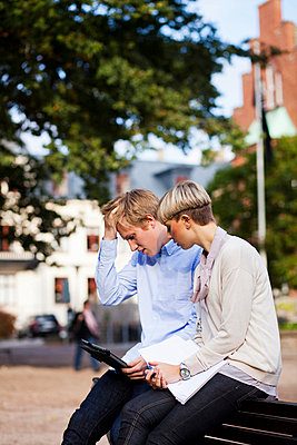 Two young university students using digital tablet at college campus - p426m747287f by Astrakan