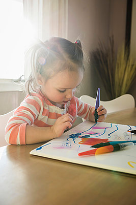 Female toddler at table drawing in sketchbook - p429m1408244 by Mike Tittel