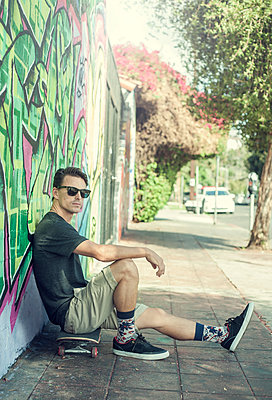 Portrait of young man sitting on skateboard, leaning against graffitied wall - p429m1450713 by Seb Oliver