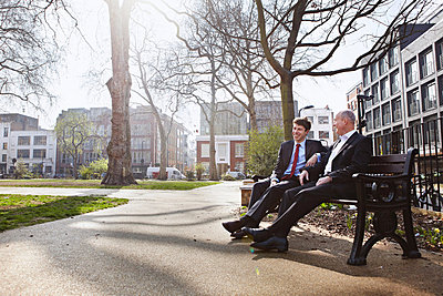 Two businessmen sitting on park bench - p429m803580f by Liam Norris
