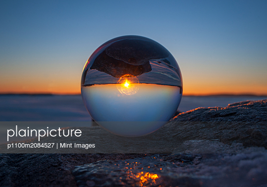 Close up of sunset horizon inverted in glass sphere,Gananoque, Ontario, Canada - p1100m2084527 by Mint Images