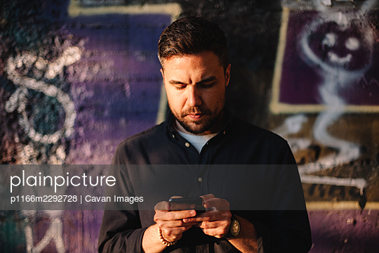 Serious man using smart phone standing against wall in city - p1166m2292728 by Cavan Images