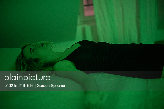 Woman lying on bed - p1321m2181616 by Gordon Spooner