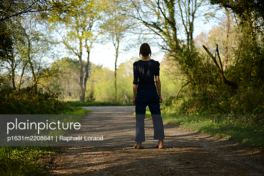 young woman on a forest road - p1631m2208641 by Raphaël Lorand