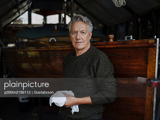 Portrait of a senior man with cloth at wooden boat in a boathouse - p300m2156112 by Gustafsson