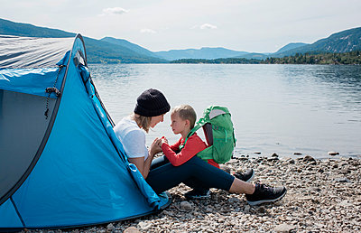 mother holding sons hands and smiling sat in a tent camping by the sea - p1166m2138072 by Cavan Images