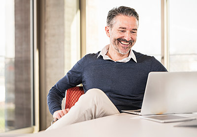 Smiling mature businessman sitting at desk in office using laptop - p300m2160313 by Uwe Umstätter